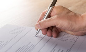 hand with pen writing survey