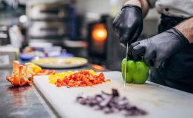 a worker's hands chopping veggies
